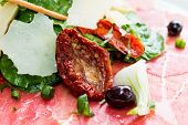 Fresh Sliced raw beef meat with leaf lettuce on the table
