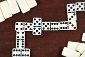 stock photo of spinner  - line of play in domino game on wooden table - JPG