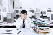 image of overwhelming  - Portrait of exhausted businessman in an office - JPG