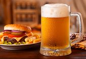 stock photo of condensation  - cold mug of beer and plate with hamburger - JPG