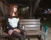 Sad Asian Woman On A Park Bench