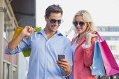Stylish young couple looking at smartphone holding shopping bags on a sunny day in the city