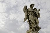 Marble statue of angel in front of heavenly clouds in Vatican