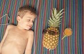 Happy child and pineapple sunbathing over a towel