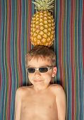 Happy child with sunglasses and pineapple in head