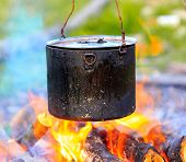 Smoked tourist kettle on campfire