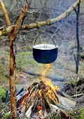 tourist kettle on campfire in forest