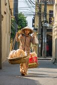 HOI AN, VIETNAM - MARCH 31: Unidentified old woman in traditional Vietnamese clothes carrying busket