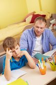 Portrait of pensive schoolboy and his father making schoolwork at home