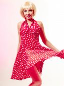Beautiful Pinup Girl In Blond Wig And Retro Red Dress Dancing. Party.
