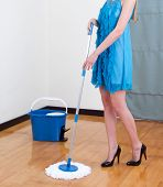 woman in beautiful dress mopping the floor