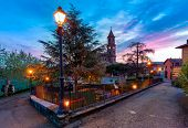 Small town square with illuminated lampposts and parish church on background under beautiful morning