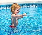 smiling cute  baby girl swims  in the pool in  summer