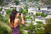 Beautiful woman taking a photo of traditional houses in Gjirokaster, Albania.