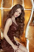 Glamorous Fashionable Woman With Long Wavy Hair. Model Posing On Armchair, Beauty And Fashion Concep