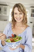 Mid age woman eating salad