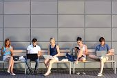 stock photo of bench  - College students internet computer addiction sitting bench outside campus summer - JPG