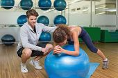 Trainer watching his client using exercise ball at the gym