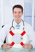 Confident Doctor Holding Lifebuoy In Clinic