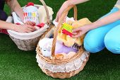 Women holding laundry baskets with clean clothes, towels and pins, on green grass background
