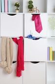 Beautiful white drawers and shelves with different home related objects