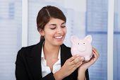 Happy Businesswoman Holding Piggybank In Office