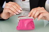 Businesswoman Putting Coin Into Pink Purse