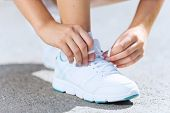 Close up of woman in sport wear tying shoelace