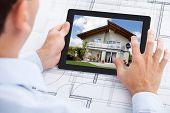 Architect Analyzing House On Digital Tablet Over Blueprint