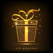 Shiny golden gift box with ribbon on brown background for muslim community festival Eid Mubarak cele