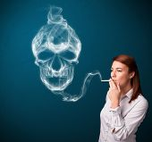 Pretty young woman smoking dangerous cigarette with toxic skull smoke