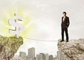 Businessman standing on the edge of mountain with a shining dollar mark on the other side