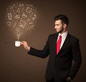 Businessman standing and holding a white cup with drown social media icons coming out of the cup