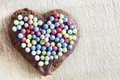 Handmade gingerbread heart decorated with colorful sugar pearls. Christmas, Valentines Day, love symbol.