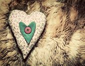 Vintage handmade plush heart pillow on the soft blanket, Valentine's Day, love concepts.