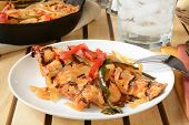 picture of poblano  - A plate of chicken asada with a cast iron serving skillet in the background - JPG