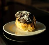 stock photo of eclairs  - Eclairs with cream in chocolate coating on a plate on a dark background - JPG