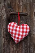 Red white checked heart hanging on an old door.