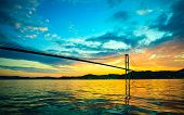 picture of suspension  - Dramatic sunset cloudy sky above a surface of the sea and long suspension bridge in Bergen Norway - JPG