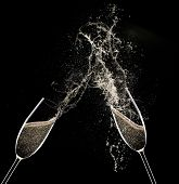 Champagne flutes on black background, celebration theme.