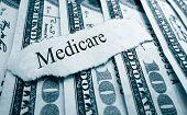 stock photo of medicare  - Medicare paper headline on hundred dollar bills - JPG