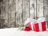 Christmas still life with gifts in snow. Wooden planks as background
