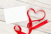Photo frame or greeting card with valentines heart shaped ribbon over wooden table background