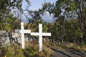 Two wooden cross on a hill.