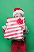 Little Kid in red costume of dwarf hiding behind red gift box