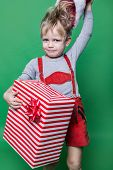 Kid in red costume of dwarf holding Christmas gift and throws Santa Claus cap. Naughty child