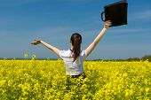 girl with a briefcase on yellow flower field