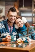 Young couple with coffee at the cafe in winter