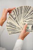 A bundle of dollars in women's hands