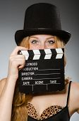 Woman with movie board wearing hat